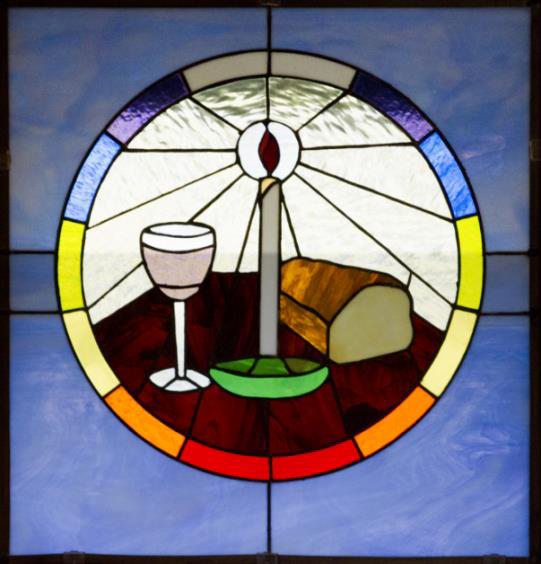 This picture is of a stained glass window, showing a lit candle, bread and wine. Around it, a circle showing rainbow colours.